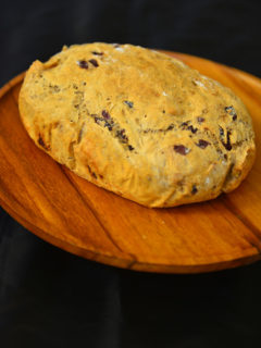 A loaf of Bread on a wooden platter in black background