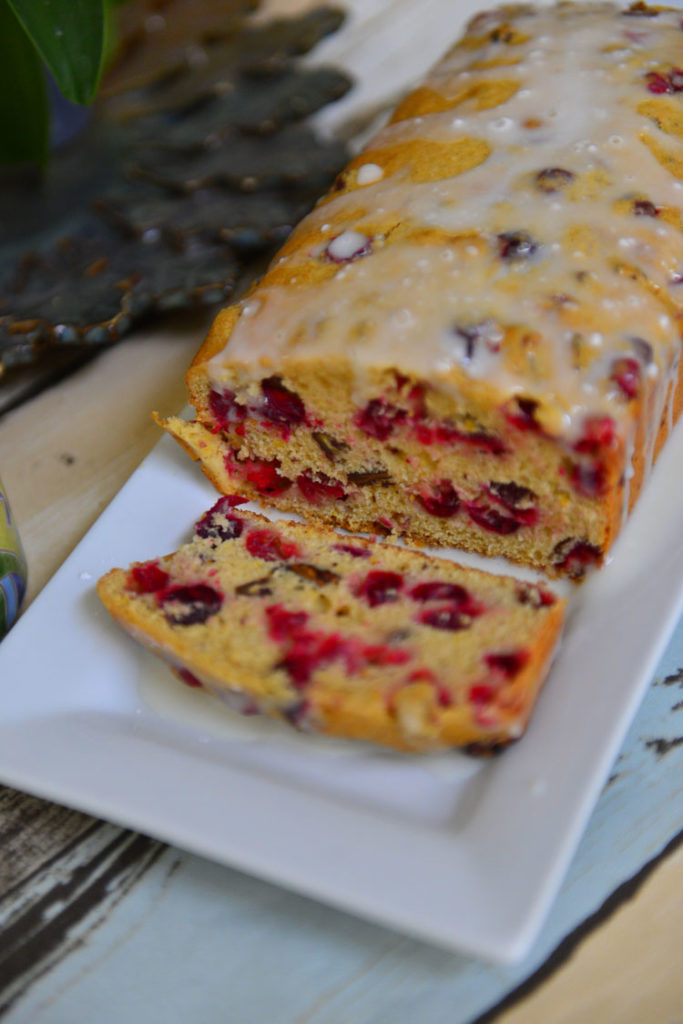 Cranberry Quick Bread in a white platter with a slice falling over