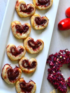 valentine palmiers arranged in a rectangular white plate with a red berry wreath nearby.