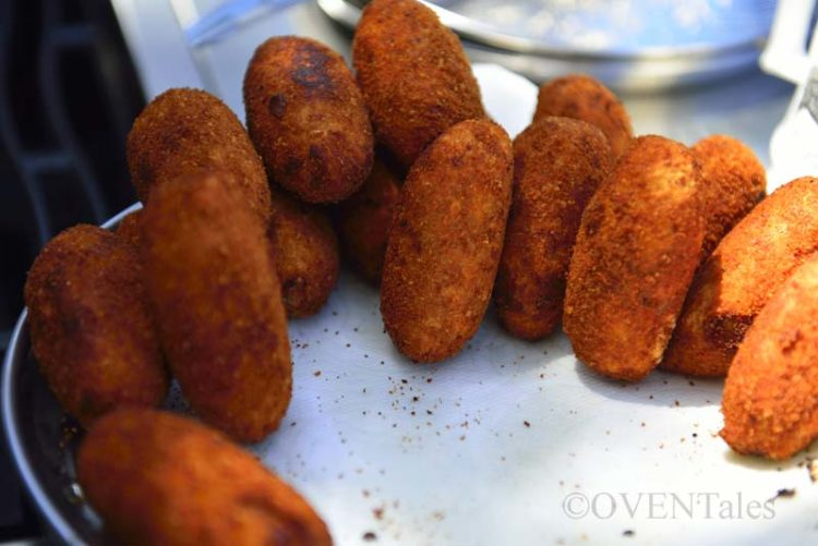 Fried croquettes draining on paper towels.