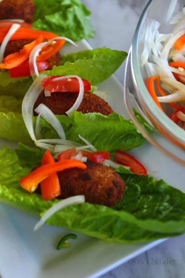 Fish croquettes on lettuce with slices of red pepper and onions