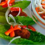 Image for pinterest - tuna cutlets on lettuce leaves with onion and onion and bell pepper salad.
