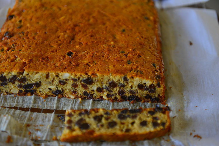 Easy Christmas Fruit Cake on a parchment sheet with a slice cut off to show the cross section