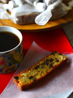 A plate with a slice of easy plum cake on a wax paper with a cup of coffee.