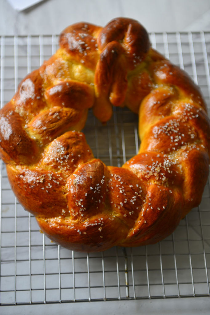 A cardamom bread wreath resting on the cooling rack