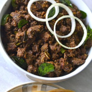 Nadan Beef Ularthiyathu in a white bowl with few onion rings on top