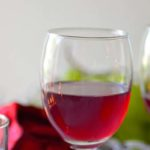 A glass of red wine and with a red glitter flower in the back ground. Caption - Home Made Grape Wine. Image for pinning