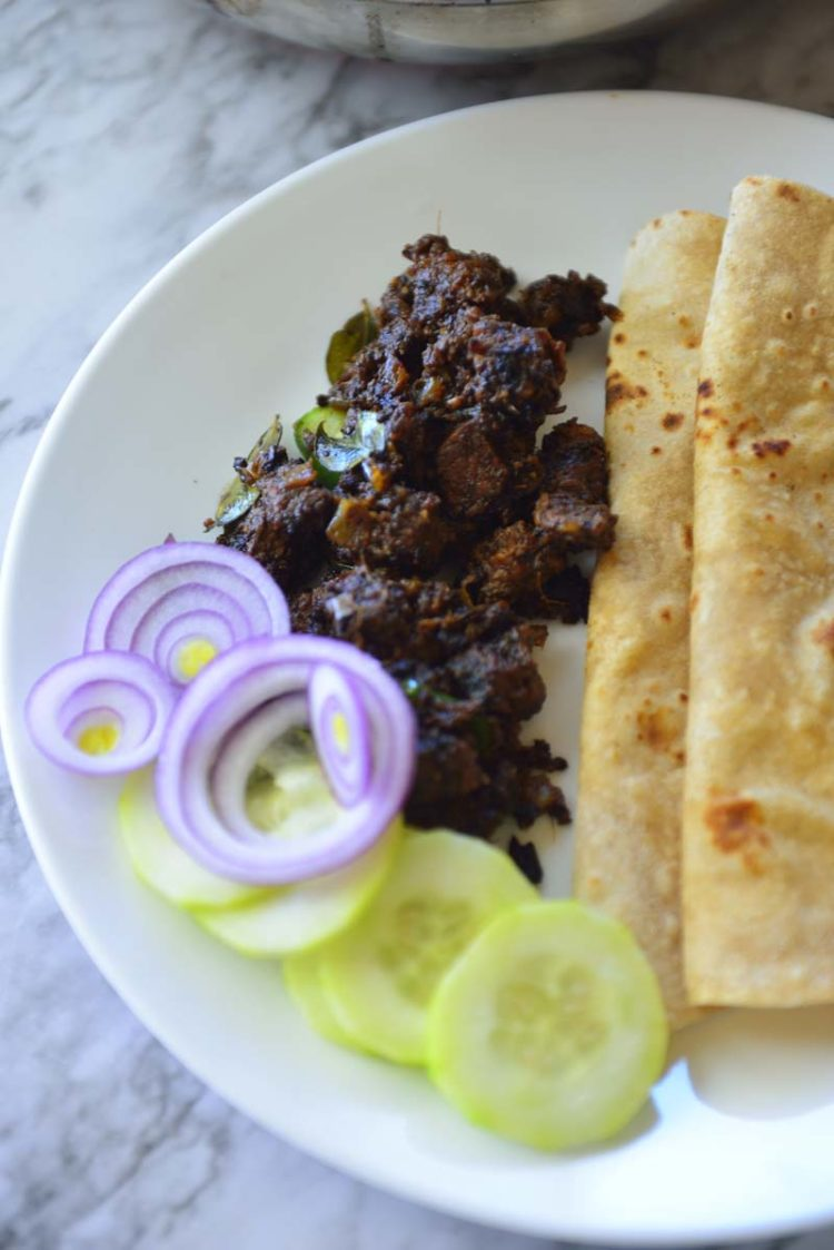A plate with flatbreads, beef fry  and a few slices of cucumbers and onions