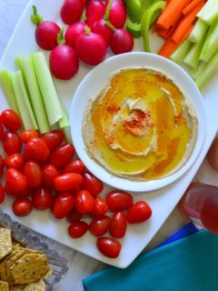 Home made hummus served with fresh veggies and crackers on a white platter