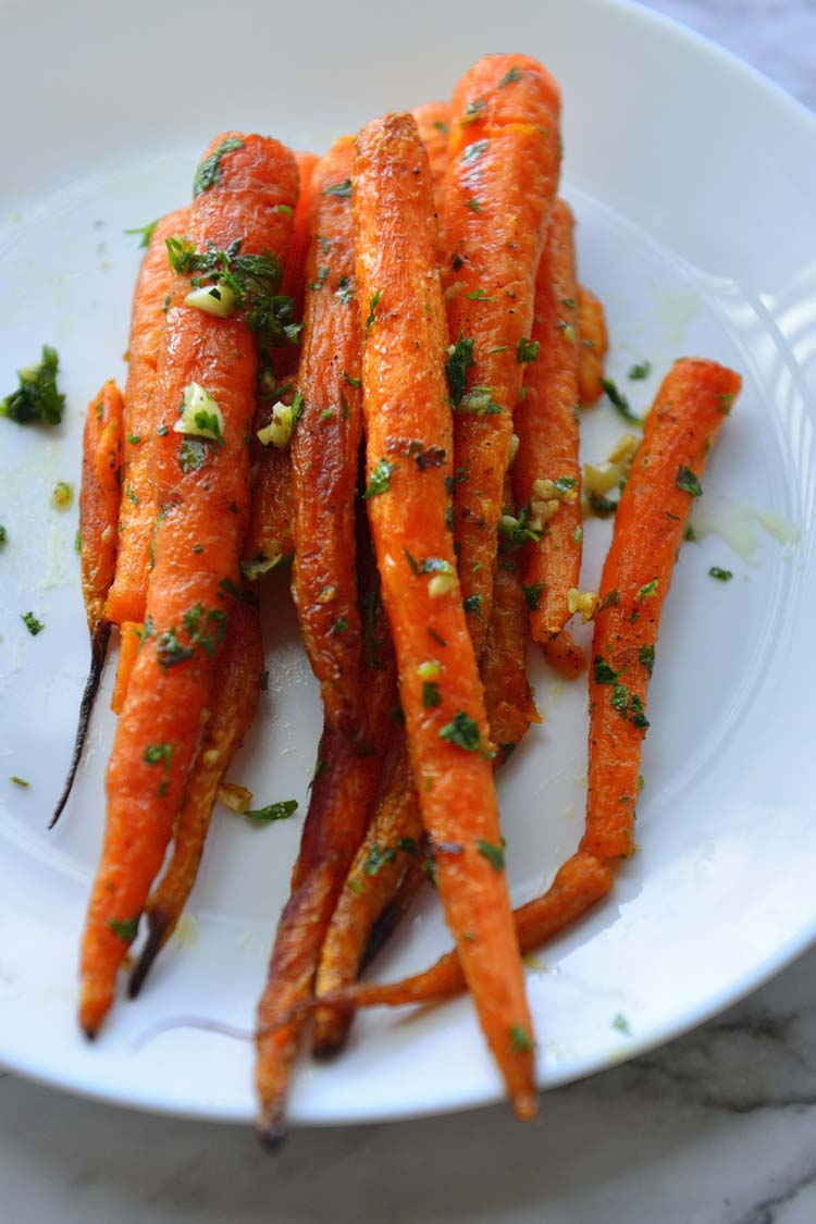 Roast carrots piled on a white plate