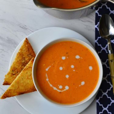 A bowl of creamy Tomato Soup with a 2 triangular slices of toast and a pot of soup next to it