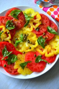 Garden Tomato Salad made with sliced colorful heirloom tomatoes on a plate