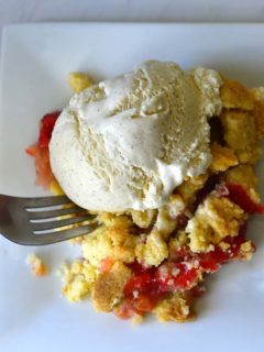 A fork scooping Strawberry Rhubarb Crumble on a white plate.