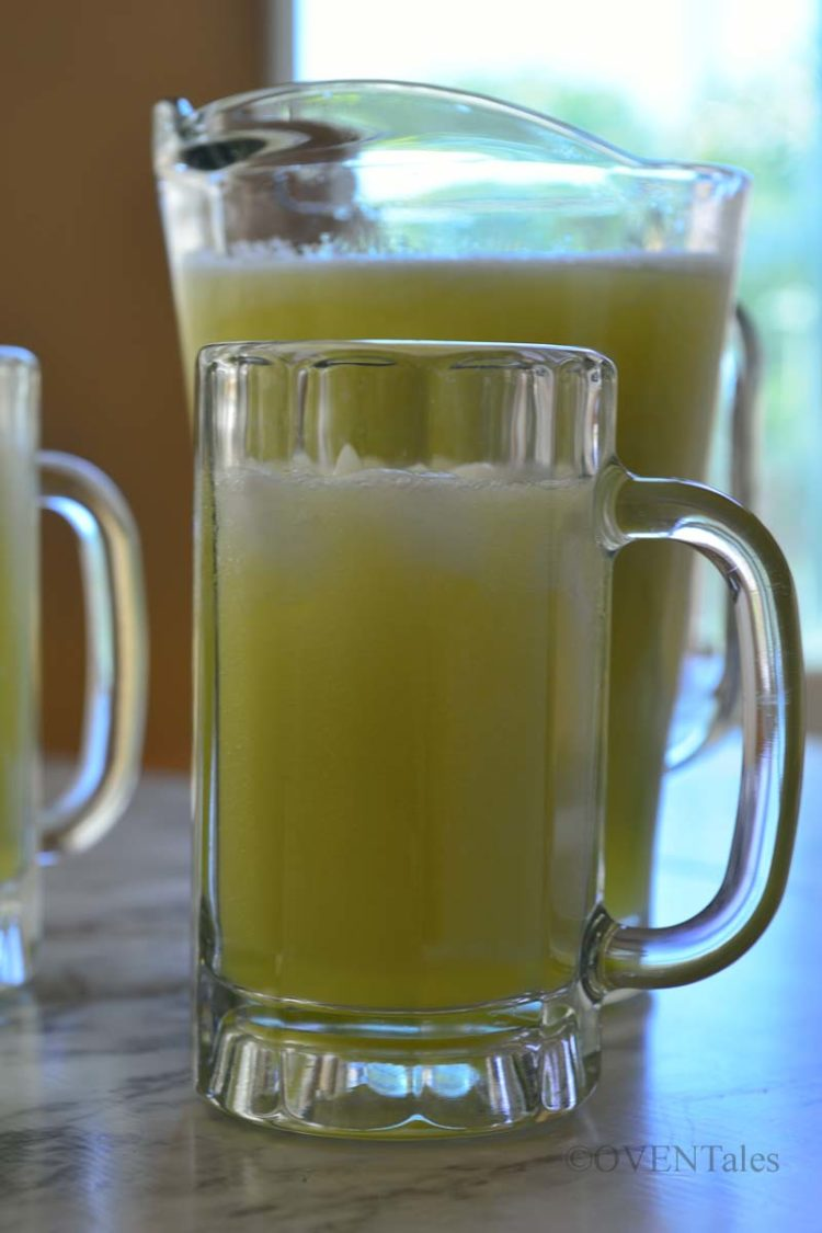 Mug of light green drink with a jar of the same drink behind it.