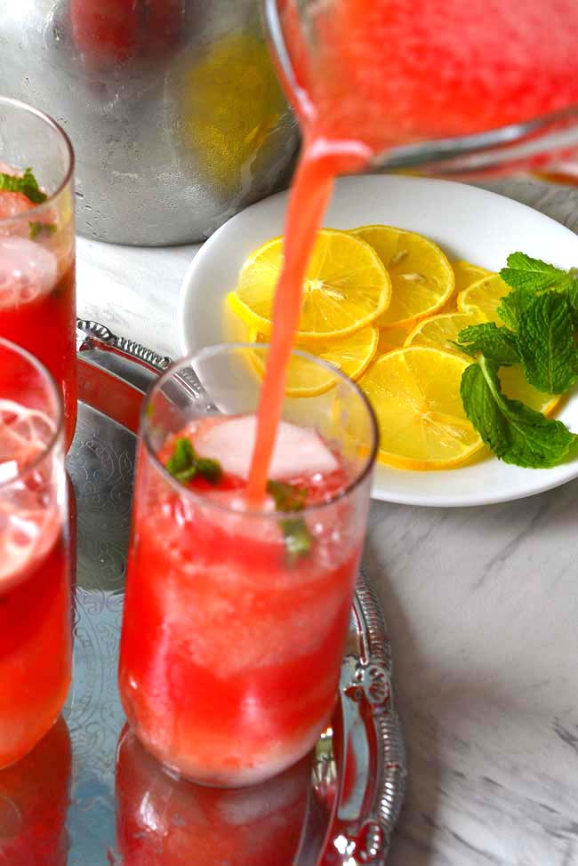 A jug of  Watermelon Agua Fresca pouring into a tall glass with garnishes of lemon and mint in teh background