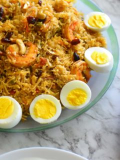 Shrimp biryani in a platterwith sliced eggs on the side.
