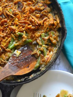 Wooden spoon scooping Green Bean Casserole from a cast iron saute pan