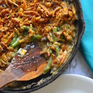 Wooden spoon scooping Green Bean Casserole from a cast iron saute pan