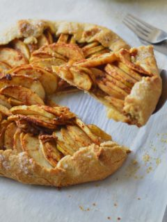 Apple galette on a parchment paper with a lice on pie server
