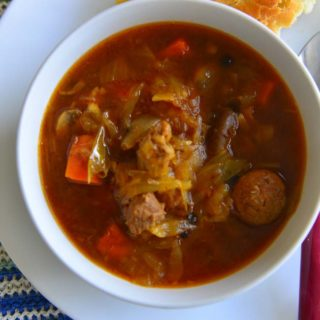 A bowl of Bigos -or the meat stew - on a plate with a slice of crusty bread on the side