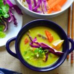 Coconut curry soup in a blue bowl. An assortment of veggies and noodles placed next to it