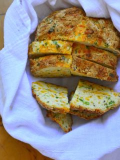 Sliced Green Onions and cheese soda bread in a bread basket .