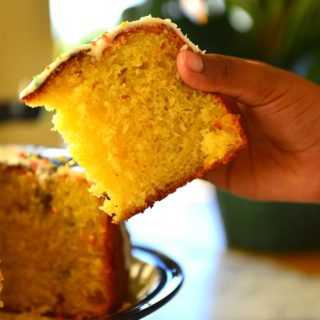 Hand holding a slice of Kulich showing its cake like crumb.