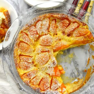 Apricot Clafoutis on a pie plate with a wedge removed.