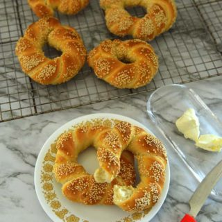 Few simit ona cooling rack and a plate with 2 simit on it and a butter bowl next to it.