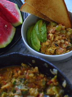 Bowl with menemen, avoccado and toast next to sliced watermelon and pan of egg scramble
