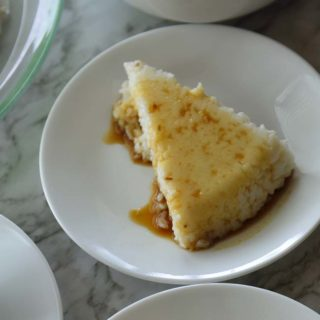 A slice of Vishu Katta on a white plate with syrup over it.