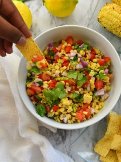 Someone trying to scoop grilled corn salsa with a chip from a white bowl