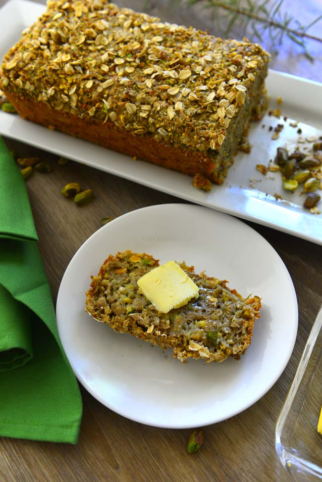 A slice of Zucchini oat bread topped with a pat of butter on a white plate with the loaf in the background