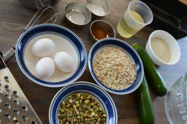 Ingredients used to make zucchini bread with oats -OIL, SALT, BAKING POWDER, OATS, PISTACHIOS, SUGAR, RGGS, FLOUR ETC