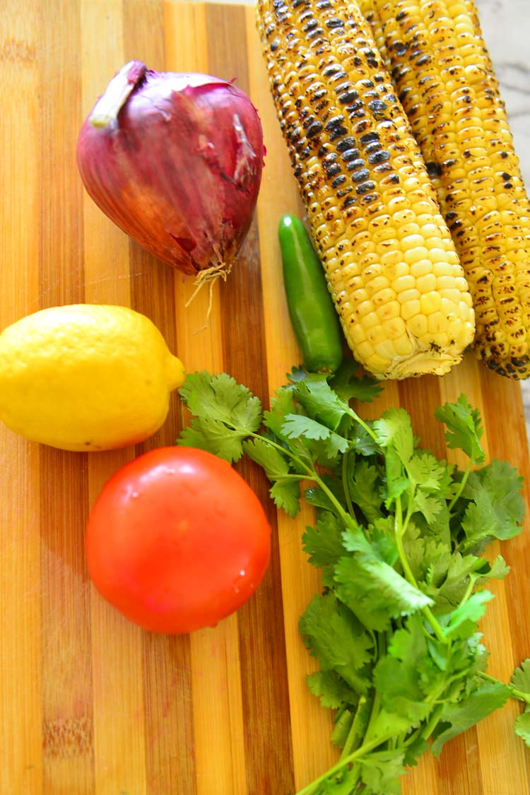 Basic  ingredinets for grilled corn salsa displayed on a cutting board - grilled corn, red onion, lemon, green chili, tomato and cilantro
