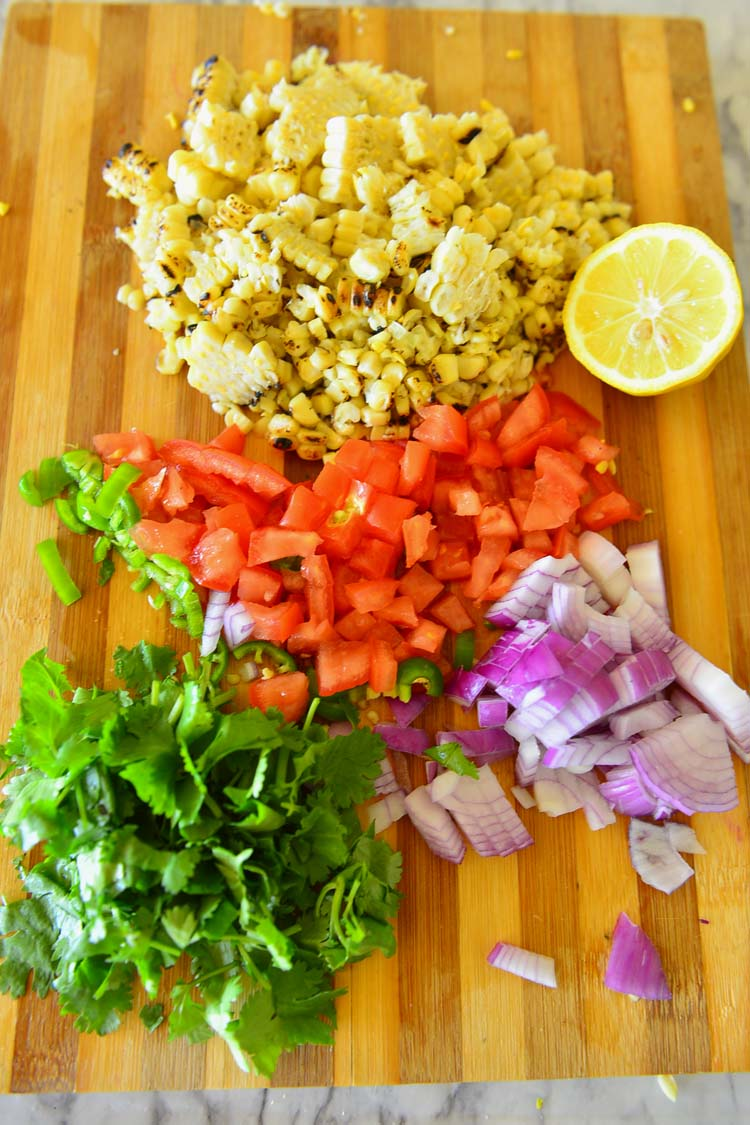 Grilled corn kernels, chopped tomatoes, onions, chilies and cilantro , and a slice of lemon for making the grilled corn salsa