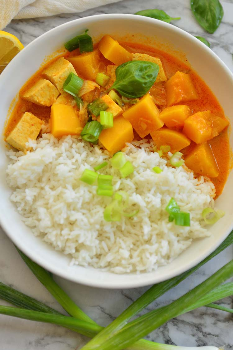 A bowl of rice and squash curry garnished with few scallions and basil leaves