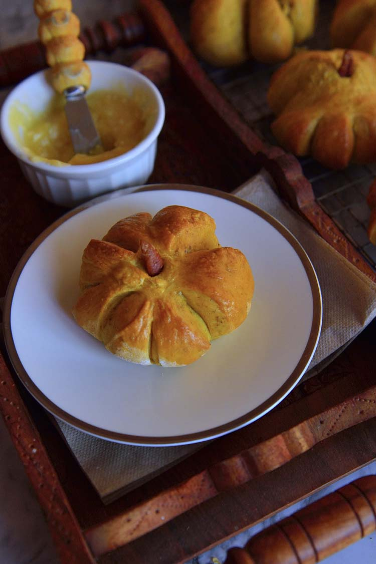 A pumpkin shaped roll on a plate with a bowl of spread next to it