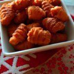 A bowl of kulkuls on table decorated for Christmas - Caption 'kulkul- Fried Sweet Curls'