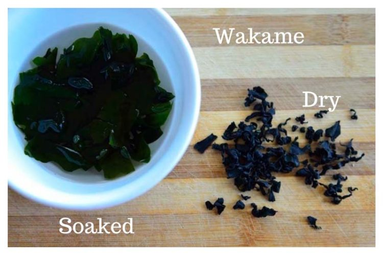 Wakame soaking in a bowl with a few dry wakame next to it
