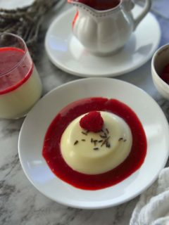 Lavender Panna Cotta in raspberry sauce on a white plate. Sauce cup and more pudding cups next to it.