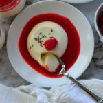 Pinnable image of lavender panna cotta on a white plate with red sauce around it . A spoon dipping into it and captioned - Lavender Panna Cotta With Raspberry Sauce