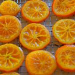 Candied orange slices on a cooling rack with caption 'Candied Orange Slices'.