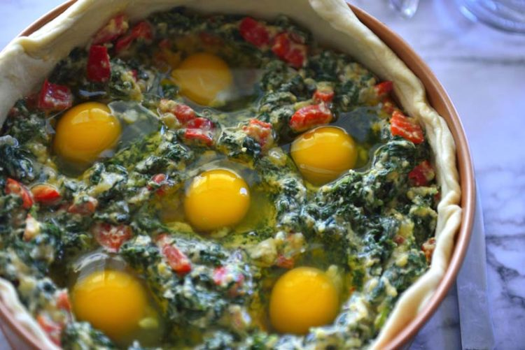 Egg and spinach filling in the pie shell uncovered.