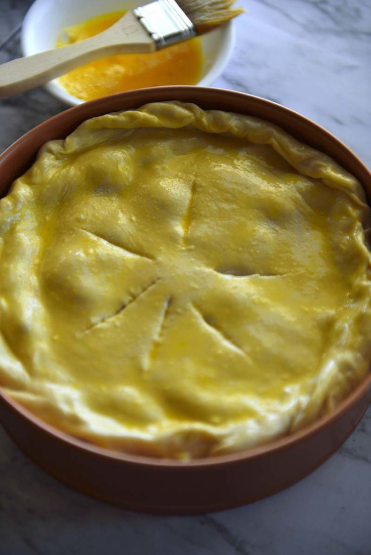 Unbaked torta pasqualina in a springform pan, fully assembled, brushed with eggwash .