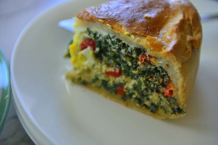 A slice of the spinach and egg pie on a white plate.