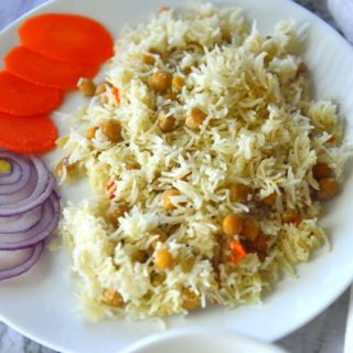 Chickpea pilaf in a white plate with slices of onions and carrots. A bowl of chutney next to it.