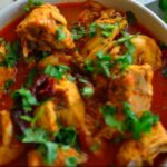 """Image for pinning - chicken curry in a bowl with bread flat breads on the side and caption """"Chicken Madras - Easy Instant Pot Verion""""."""