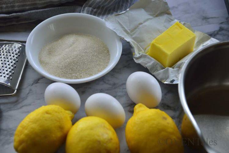 lemon, eggs, butter, sugar, zester and a pan.