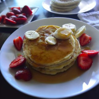 Stack of pancakes on a plate with fruits and syrup.